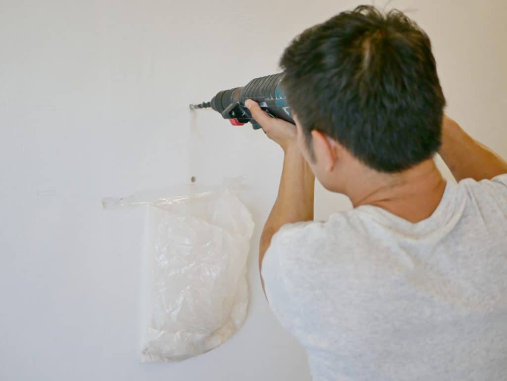 Man drilling into concrete wall to hang a picture