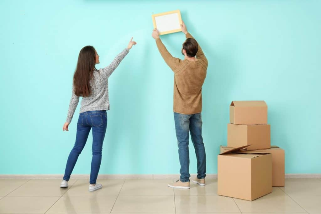 Couple choosing where to hang a picture on a concrete wall