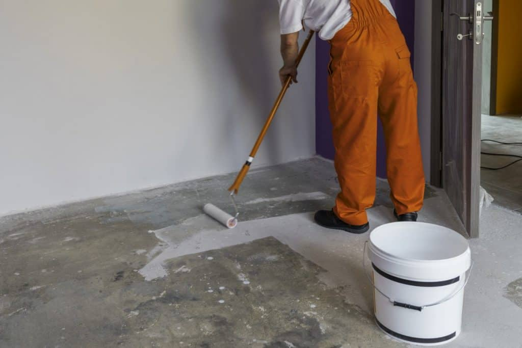 Man applying stain to concrete