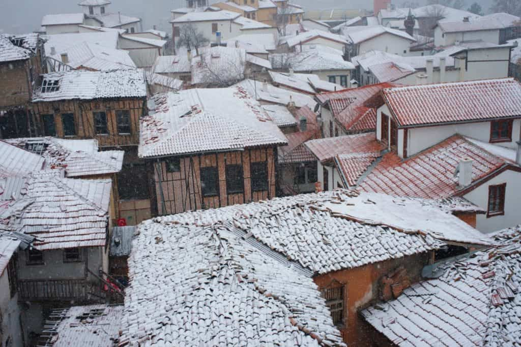 Houses with concrete roof tiles covered in snow.