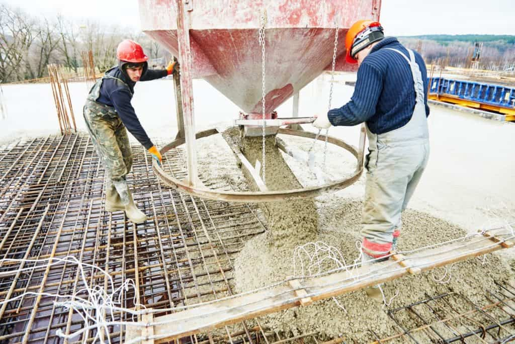 Concrete workers pour concrete to make a footing