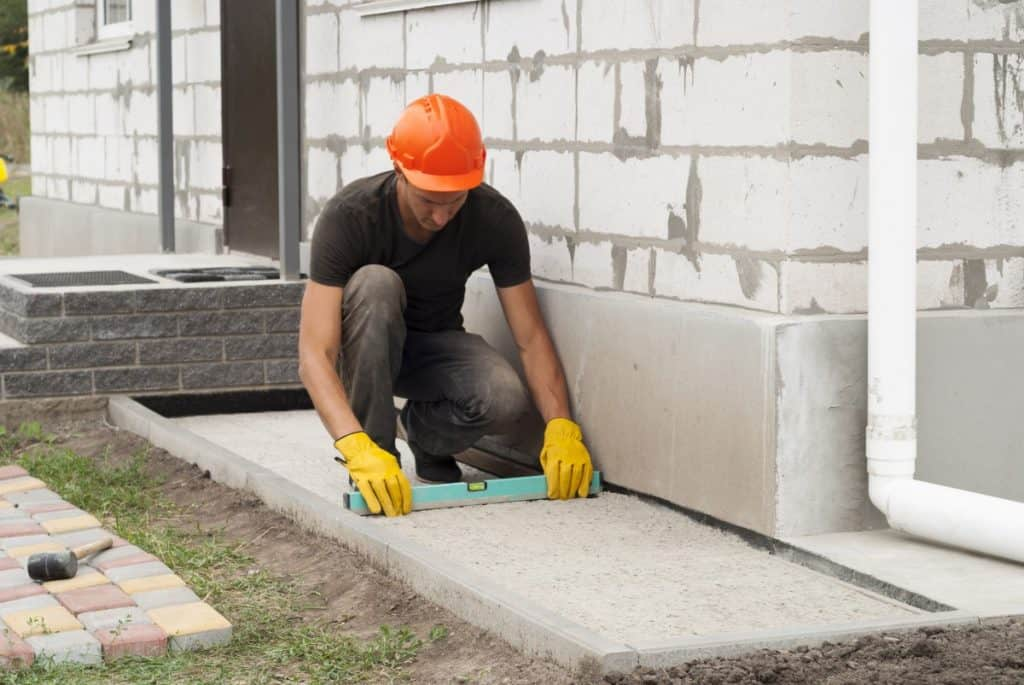 Man works on concrete house