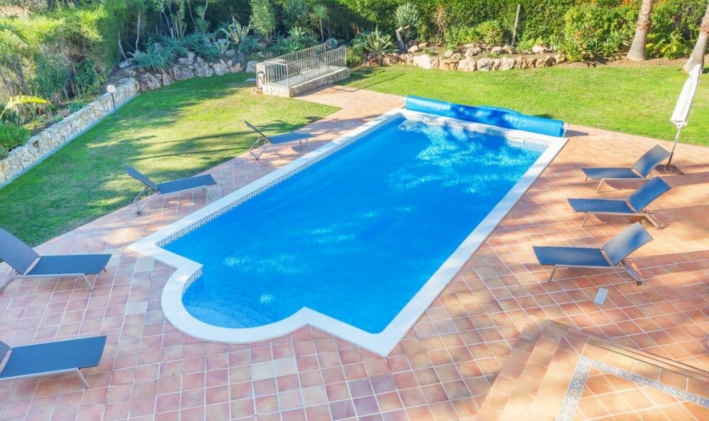 Pool decking with a simple and classy mix of smooth concrete and stamped concrete.
