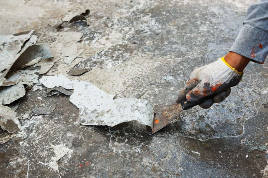 Preparing concrete floor for acid staining by scraping off old paint.