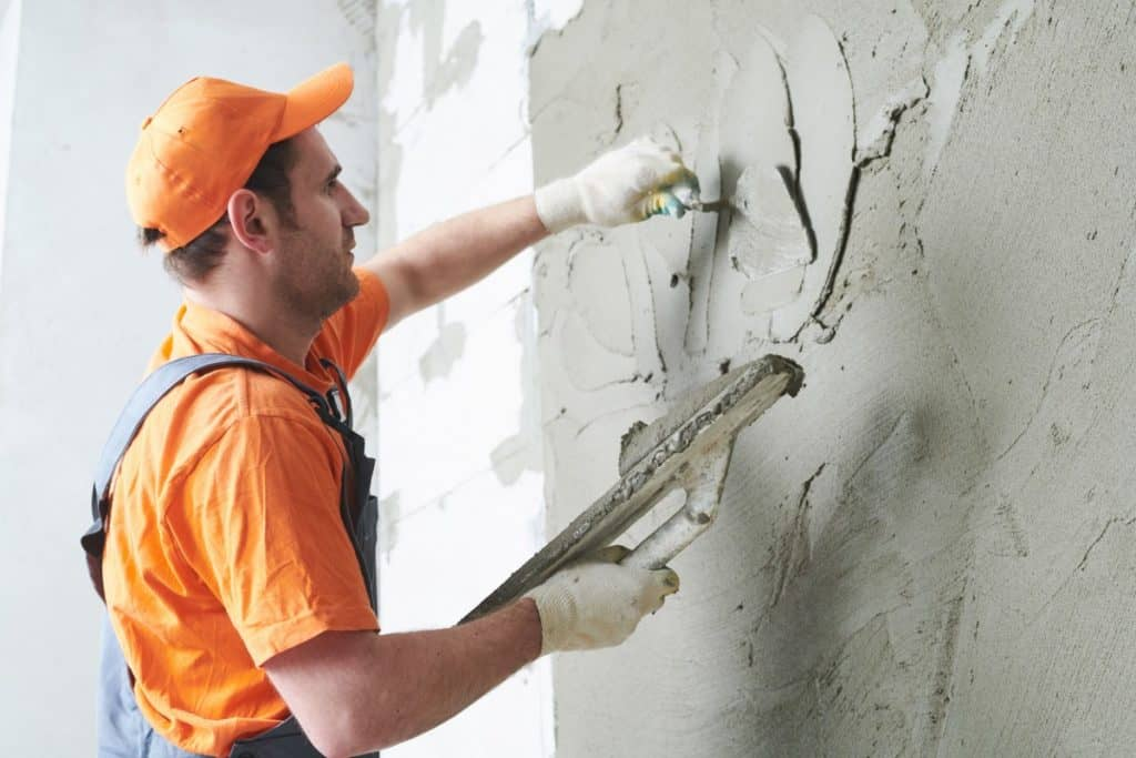 Man parging a concrete wall to cover it.
