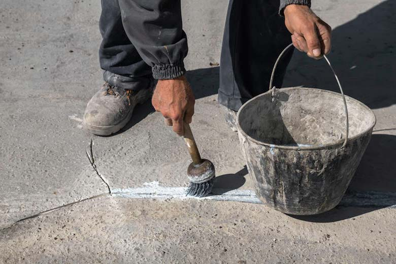 Man sealing a crack in concrete