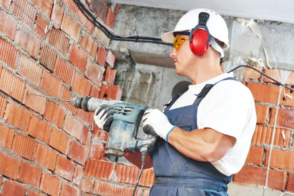 Man using a hammer drill for drilling into concrete