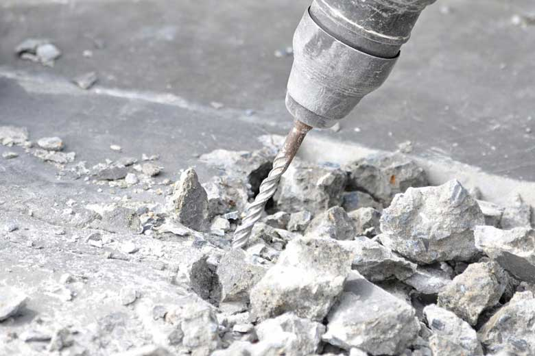 Breaking up concrete using a drill